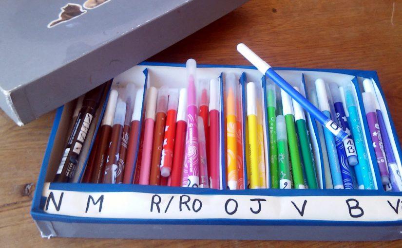 feutres rangés par couleur dans une boîte à compartiment